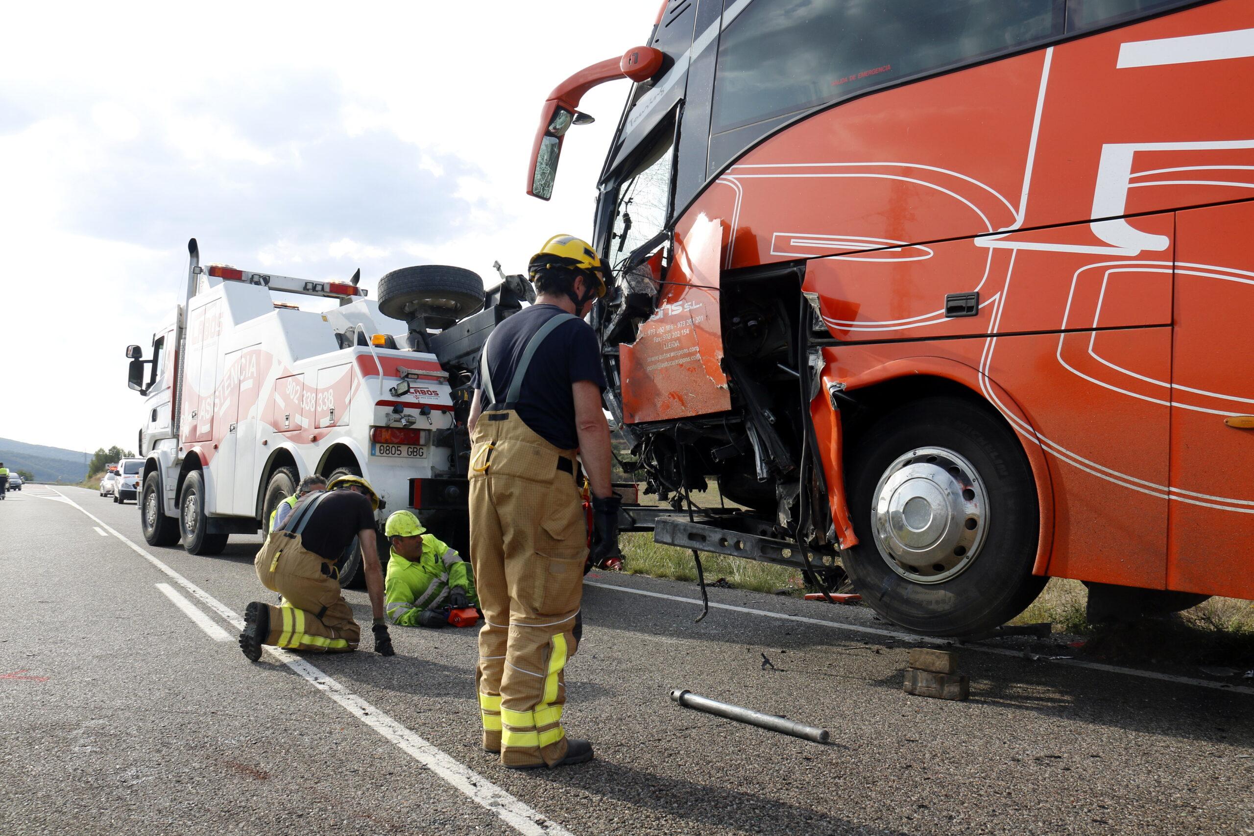 Pla general on es pot veure l'autocar que ha impactat frontalment contra una furgoneta amb el resultat d'un mort a la C-12 a Àger mentre operaris i Bombers intenten retirar-lo de la via, el 21 de setembre de 2018. (Horitzontal)