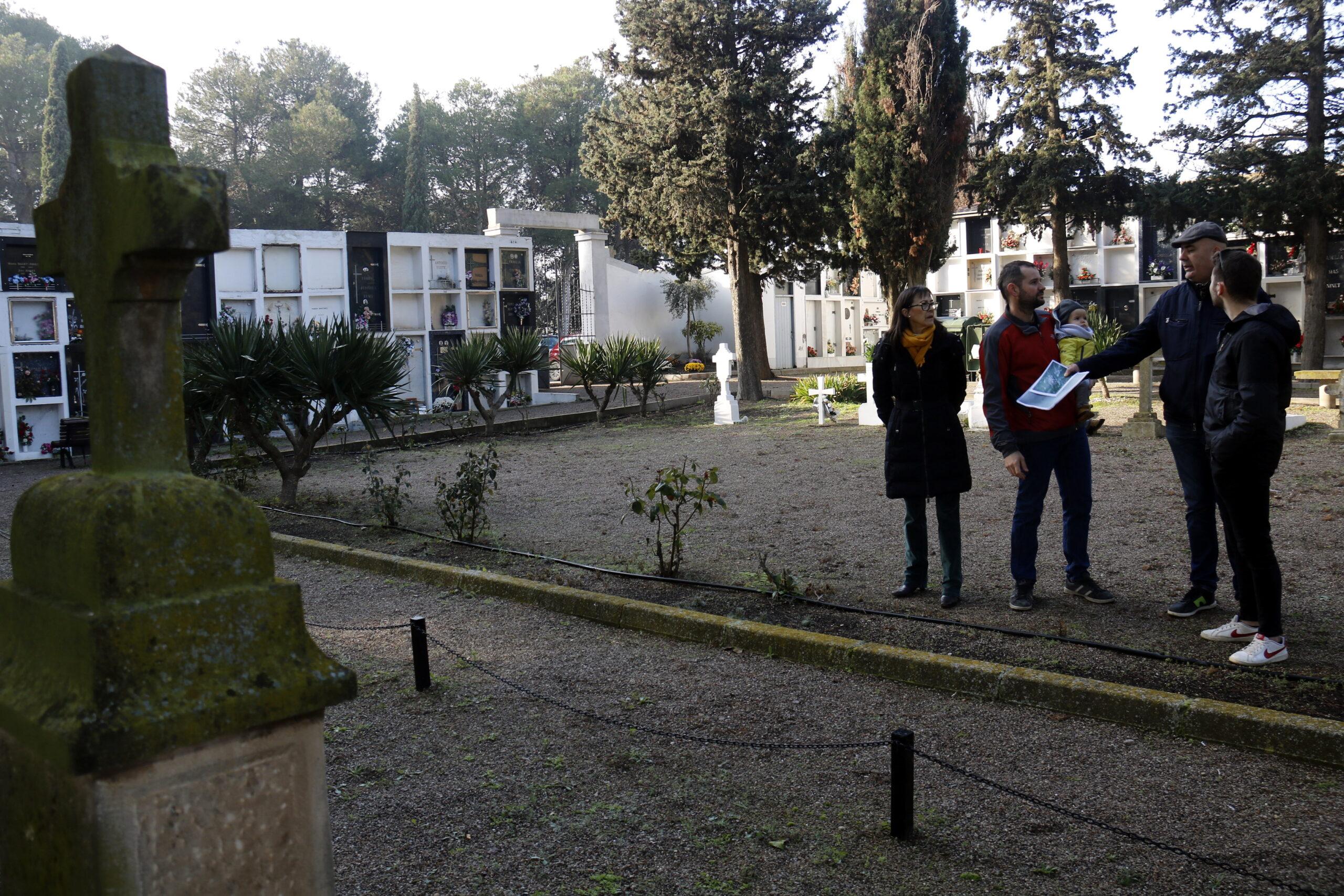 Pla obert on es pot veure la zona del cementiri de Bell-lloc d'Urgell on hi hauria una fossa de la guerra i l'alcalde i regidors en una banda mirant documentació, el 3 de desembre de 2018. (Horitzontal)