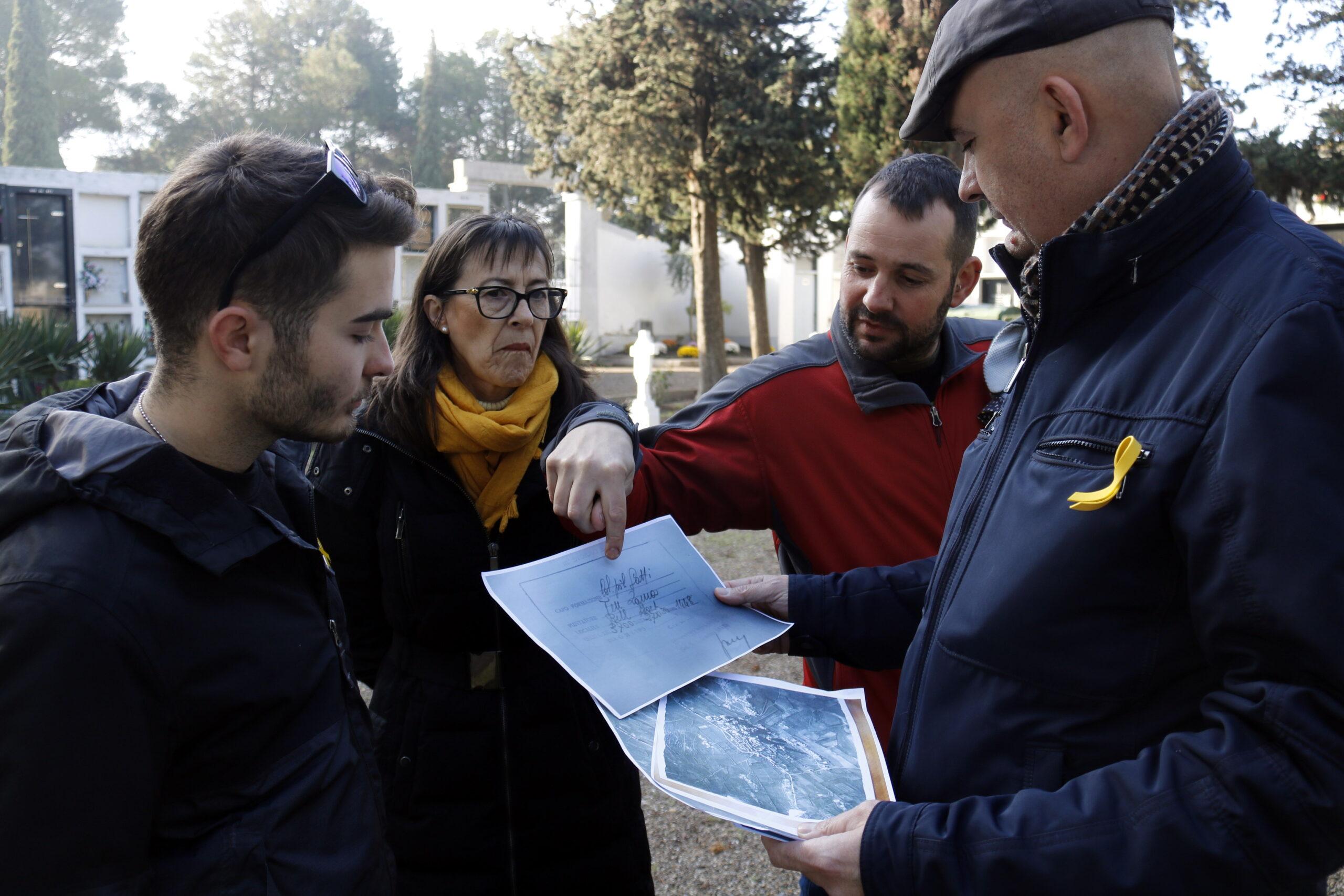 Pla mitjà on es pot veure l'alcalde de Bell-lloc i altres regidors mirant documentació sobre els bombardejos de la guerra al cementiri del municipi, on hi hauria una fossa de soldats, el 3 de desembre de 2018. (Horitzontal)