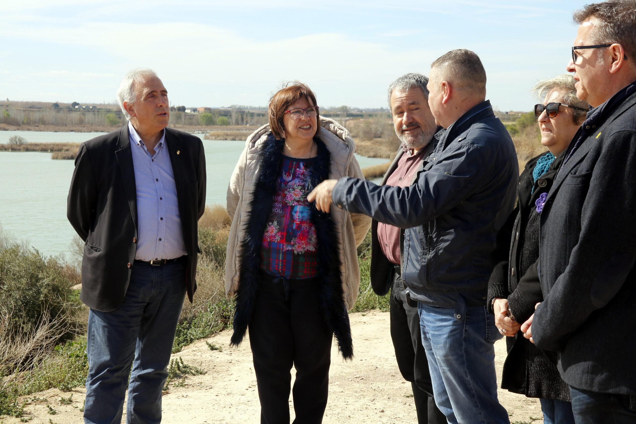 Pla mitjà on es pot veure a la presidenta de la Diputació de Lleida, Rosa Maria Perelló, acompanyada pel director de Medi Natural, Ferran Miralles, i altres membres del consorci a l'estany d'Ivars i Vila-sana, el 14 de març de 2019. (Horitzontal)