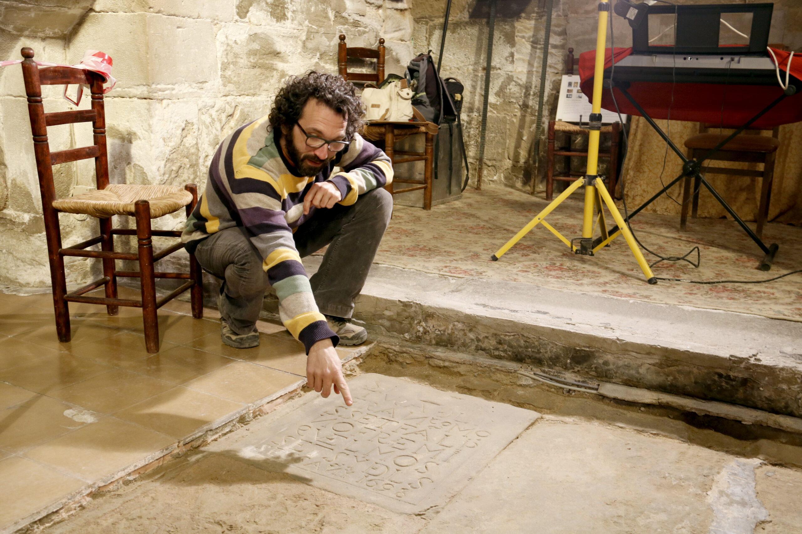 L'arqueòleg  d'ILTIRTA Arqueologia, Andreu Moya, assenyala la data que marca la làpida trobada a l'església de Santa Maria de Linyola. Imatge del 19 de març de 2019. (Horitzontal)