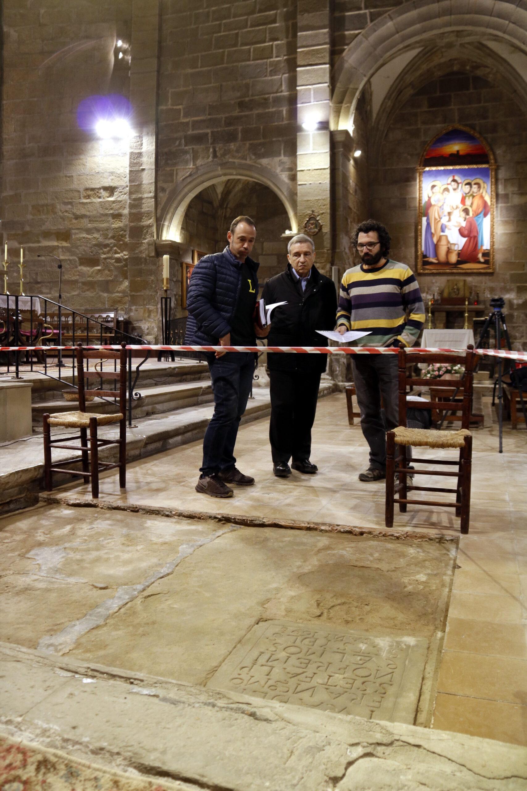 L'arqueòleg d'ILTIRTA Arqueologia, Andreu Moya; l'alcalde de Linyola, Àlex Mases, i el mossèn Pere, observen la làpida trobada a l'església de Santa Maria de Linyola. Imatge del 19 de març de 2019. (Vertical)