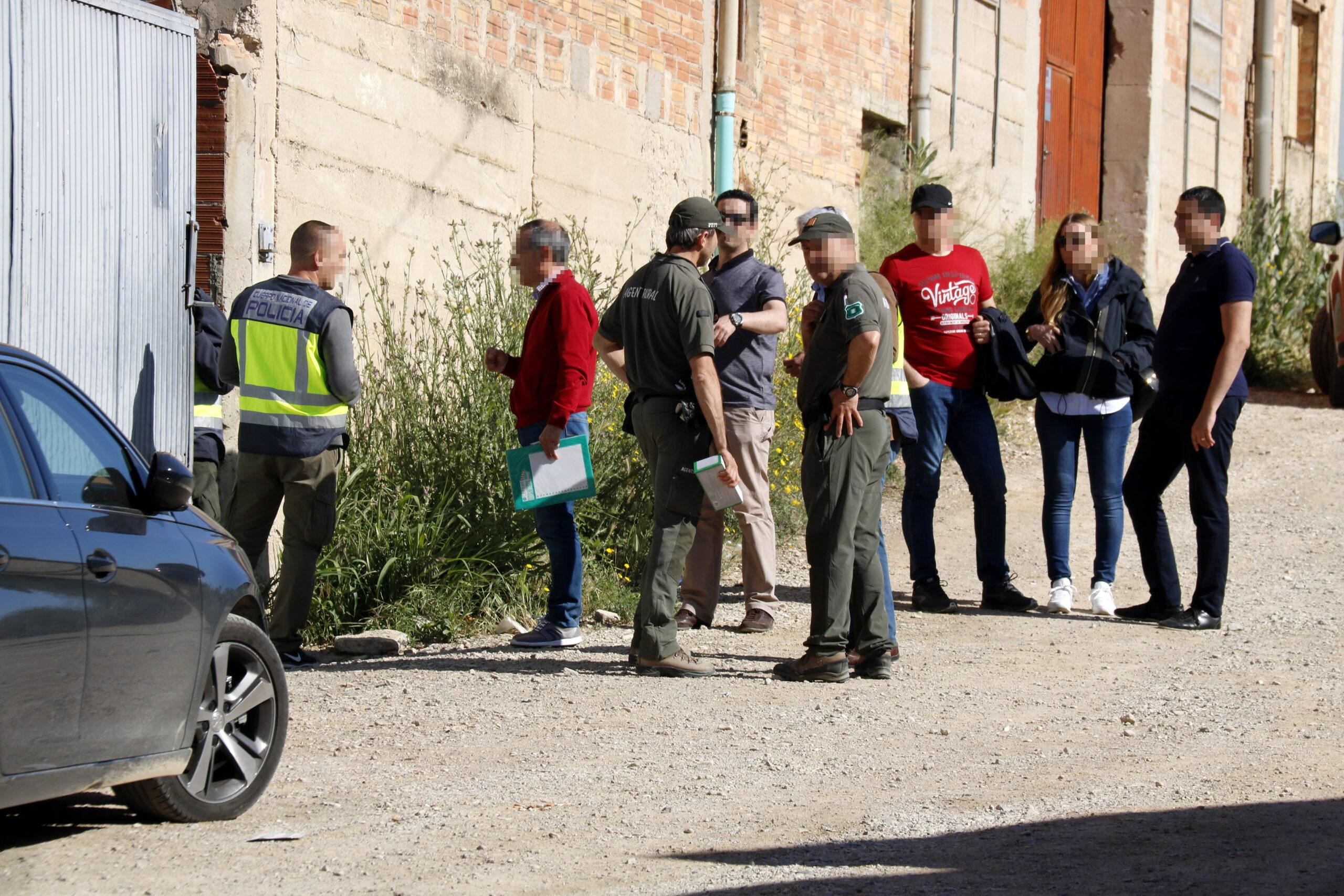 Pla mitjà on es poden veure agents de la policia espanyola amb Agents Rurals a la porta d'accés del magatzem de Bell-lloc d'Urgell on s'han detingut quatre persones per delictes de tràfic de silurs, el 14 de maig de 2019. (Horitzontal)