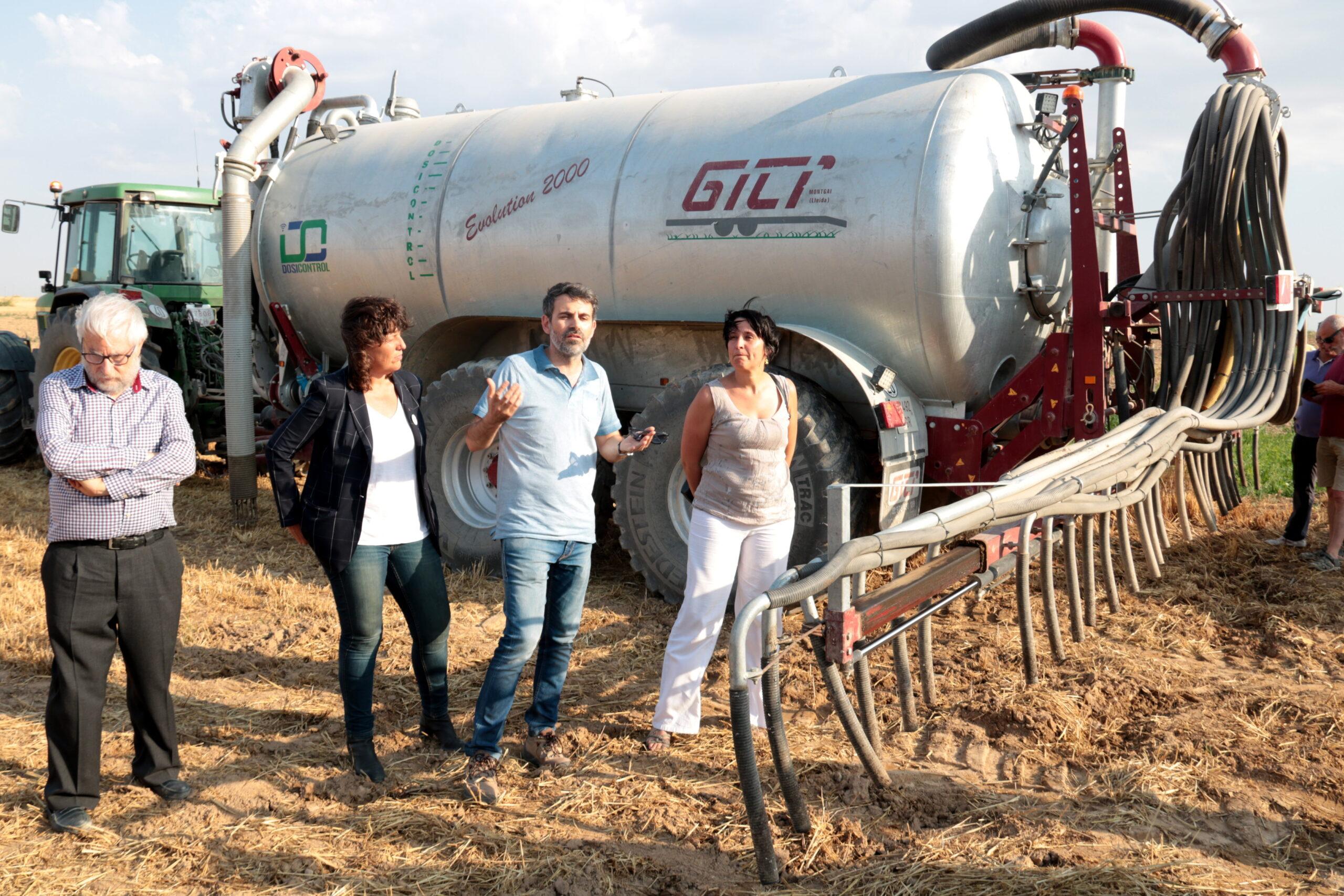La consellera d'Agricultura, Teresa Jordà, al costat d'un tractor amb un cisterna que utilitza el sistema de tubs penjants en una finca de cereal d'Albesa, el 3 de juliol del 2019. (Horitzontal)