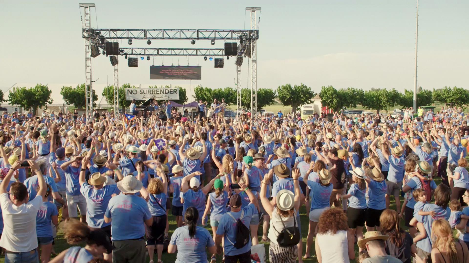 FOTOGRAMA del vídeo oficial del No Surrender Festival 3 en una imatge en que es pot veure la part central de l'escenari i els participants que cantaven, el 29 de juny de 2019. (Horitzontal)