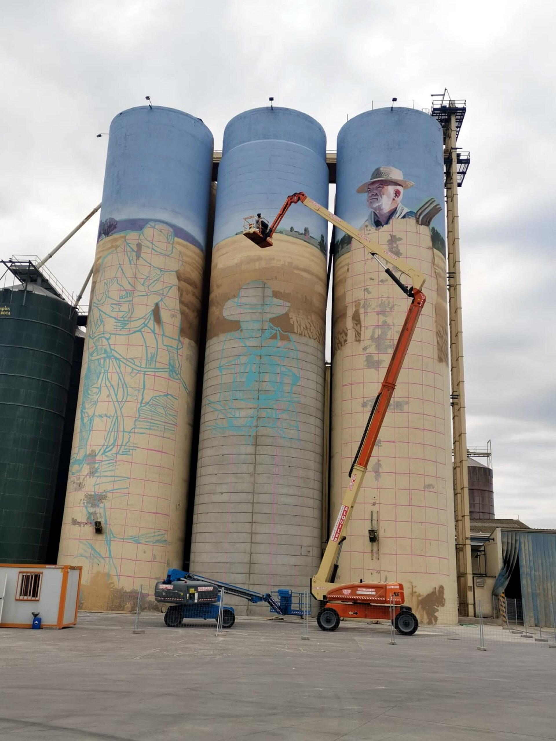 Imatge dels treballs de creació del gran mural a les sitges de la fàbrica de pinso que la Cooperativa d'Ivars té a Torregrossa, l'11 d'octubre del 2019. (Vertical)