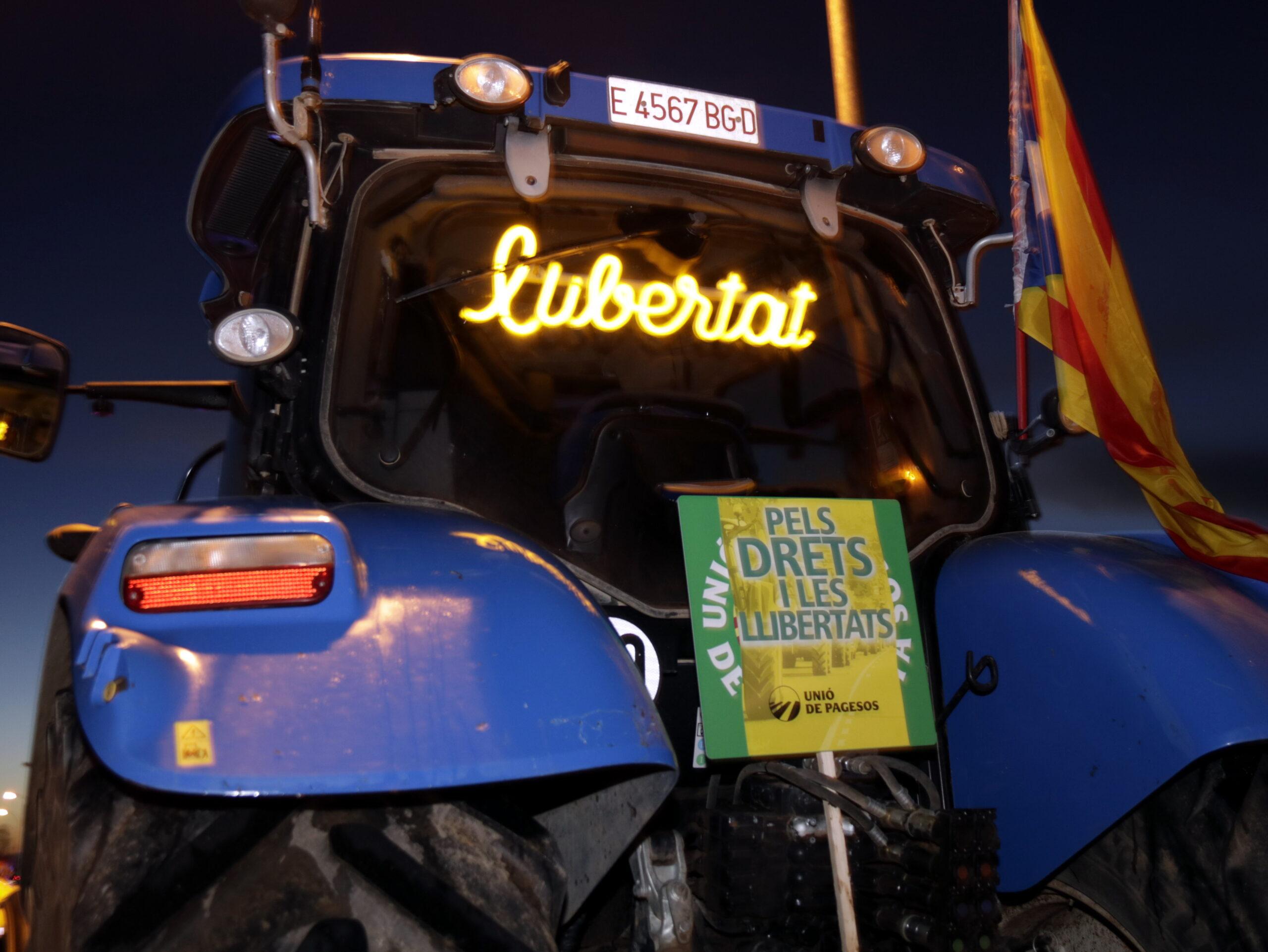 Pla curt d'un tractor que porta un panell lluminós amb la paraula 'llibertat' i un cartell de la tractorada a Mollerussa, el 21 de desembre de 2019. (Horitzontal)