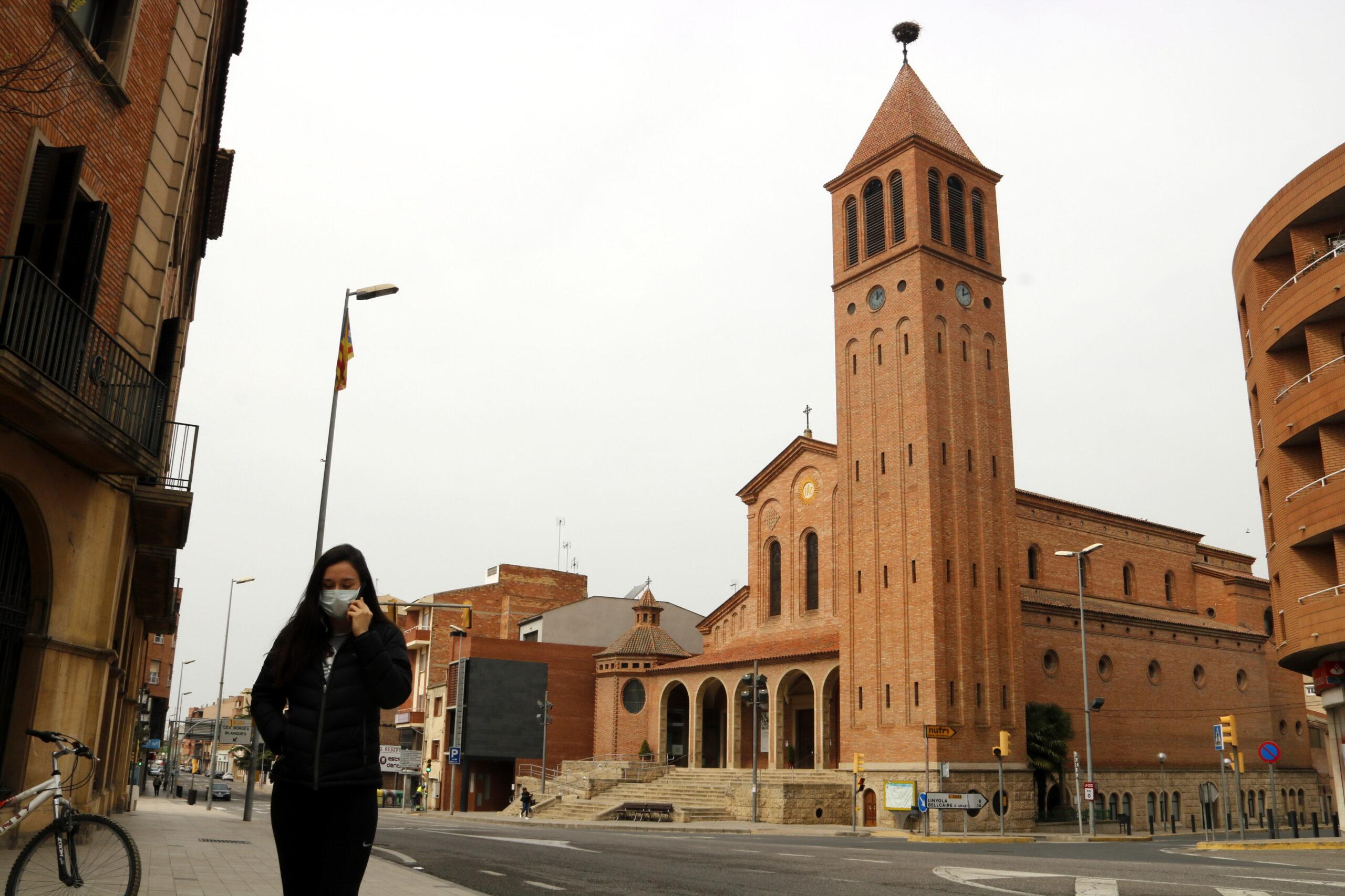 Pla general on es pot veure el campanar de la parròquia de Sant Jaume de Mollerussa i una noia caminant pel carrer amb mascareta per evitar contagis del coronavirus, el 18 de març de 2020. (Horitzontal)