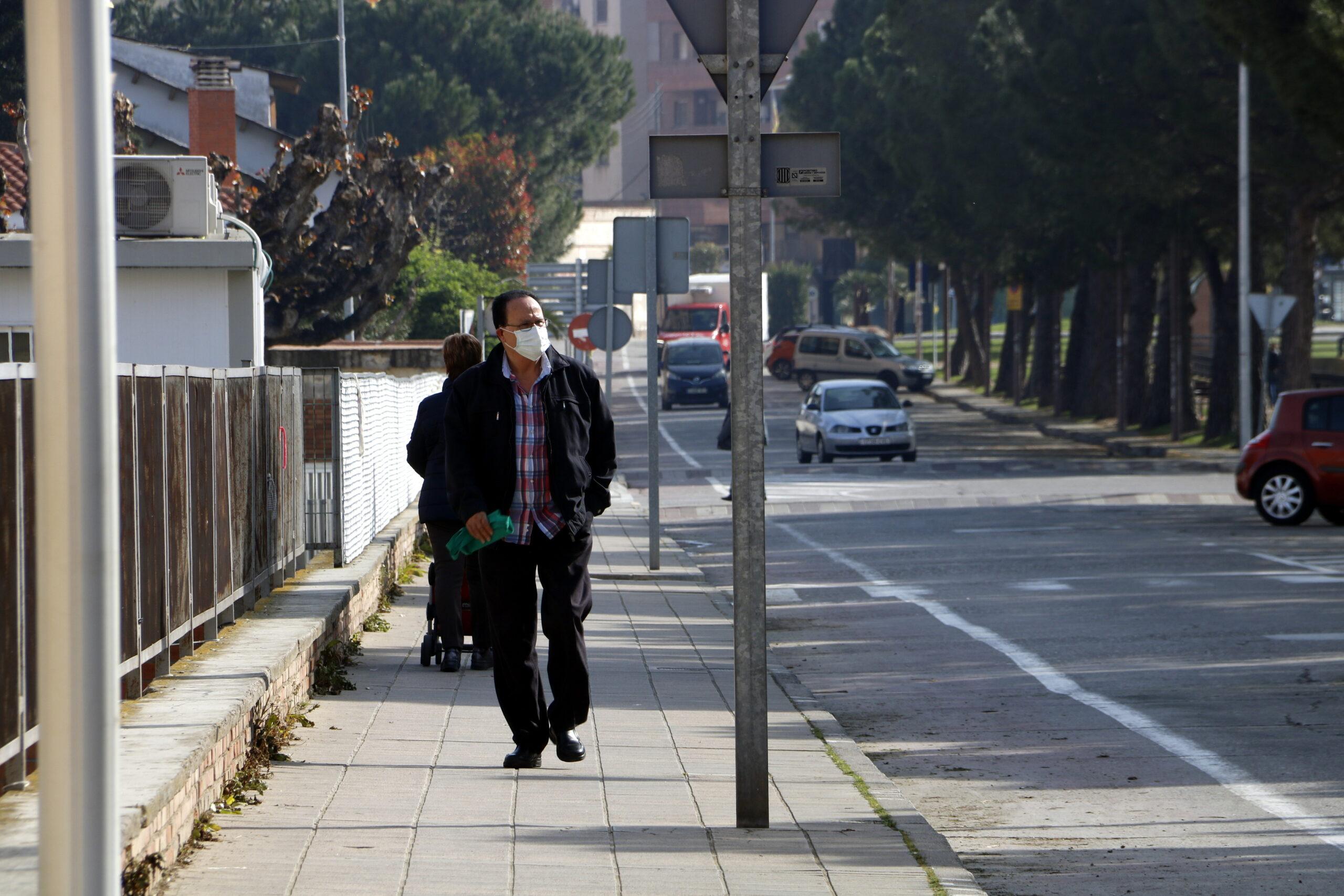 Pla mitjà on es pot veure un senyor amb màscara passant per l'avinguda del Canal de Mollerussa on s'hauria d'estar celebrant la Fira de Sant Josep, suspesa pel coronavirus, el 19 de març de 2020. (Horitzontal)