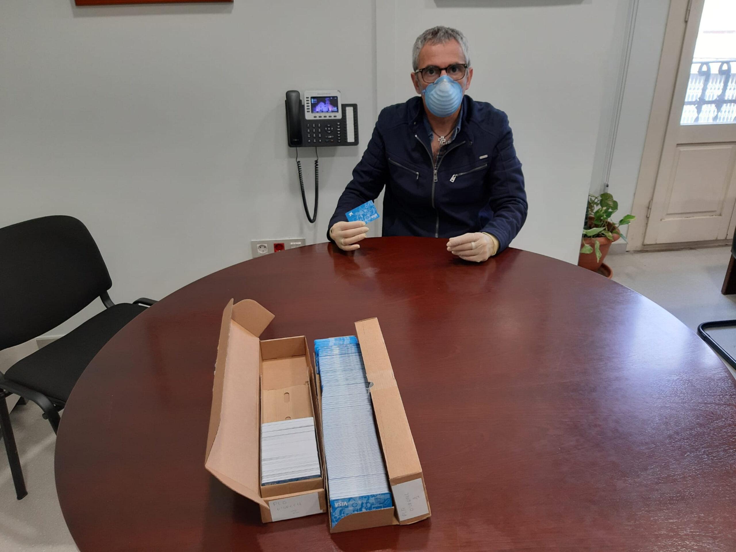 El president del Consell Comarcal del Pla d'Urgell, Rafel Panadés, amb les targetes moneder per famílies que reben ajuts de menjador. Imatge del 23 de març de 2020. (Horitzontal)