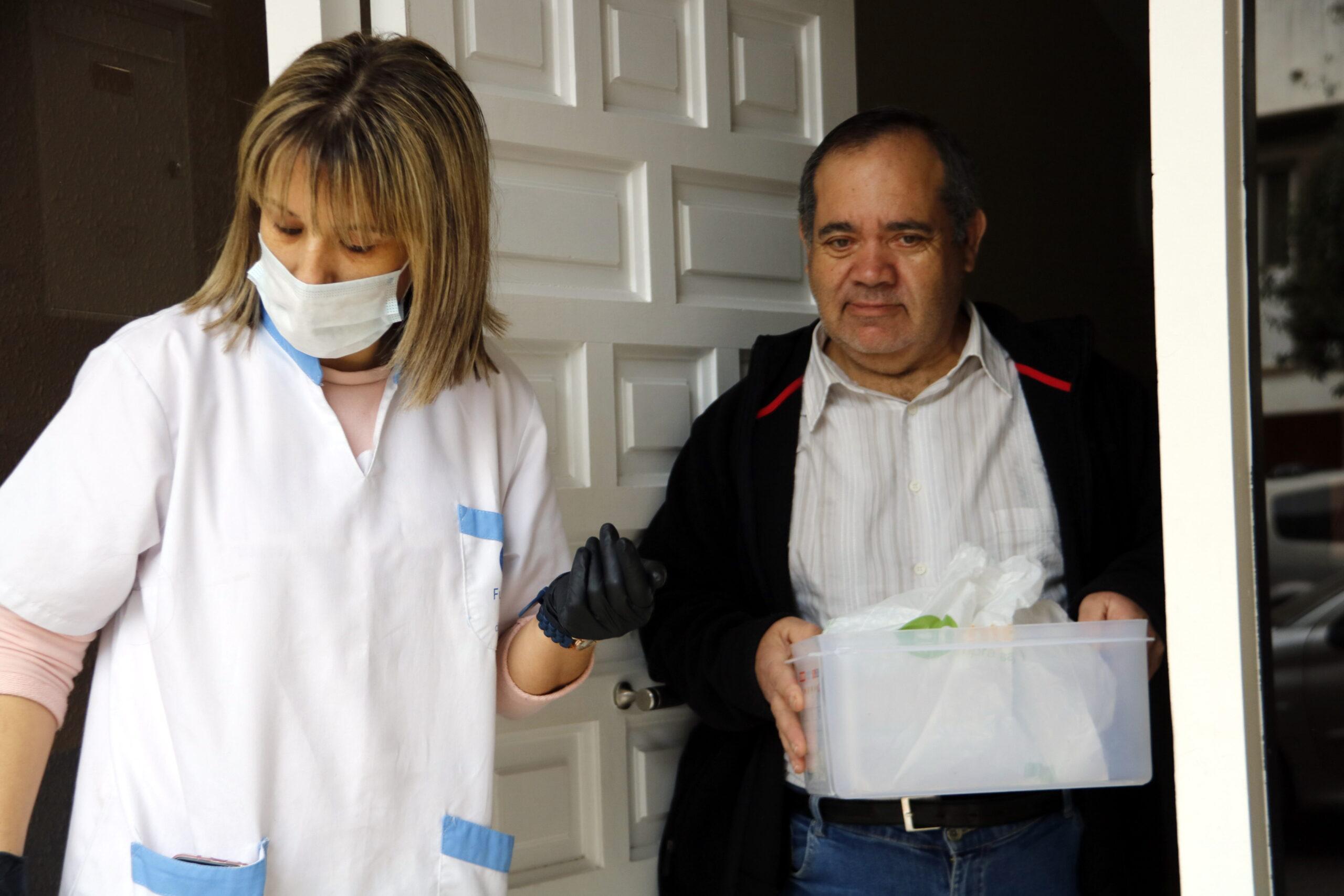 Pla mitjà on es pot veure un moment del repartiment de menjar preparat a domicili per la crisi del coronavirus, a Mollerussa, el 31 de març de 2020. (Horitzontal)