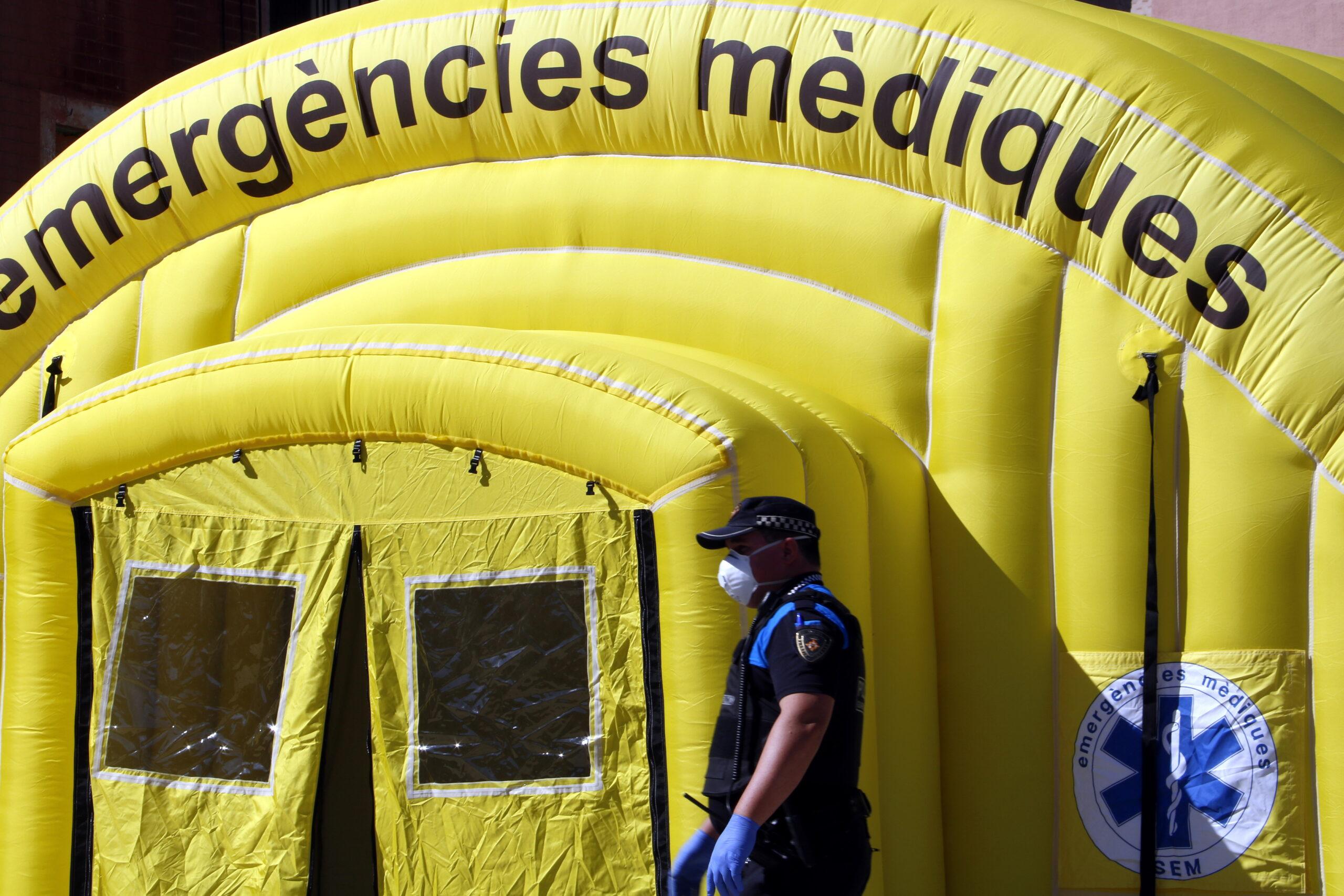 Pla mitjà on es pot veure un agent de la Guàrdia Urbana de Lleida, amb mascareta, passant per davant de la carpa medicalitzada de SEM per fer testos de covid-19 a temporers que dormen al carrer, el 19 de maig de 2020. (Horitzontal)
