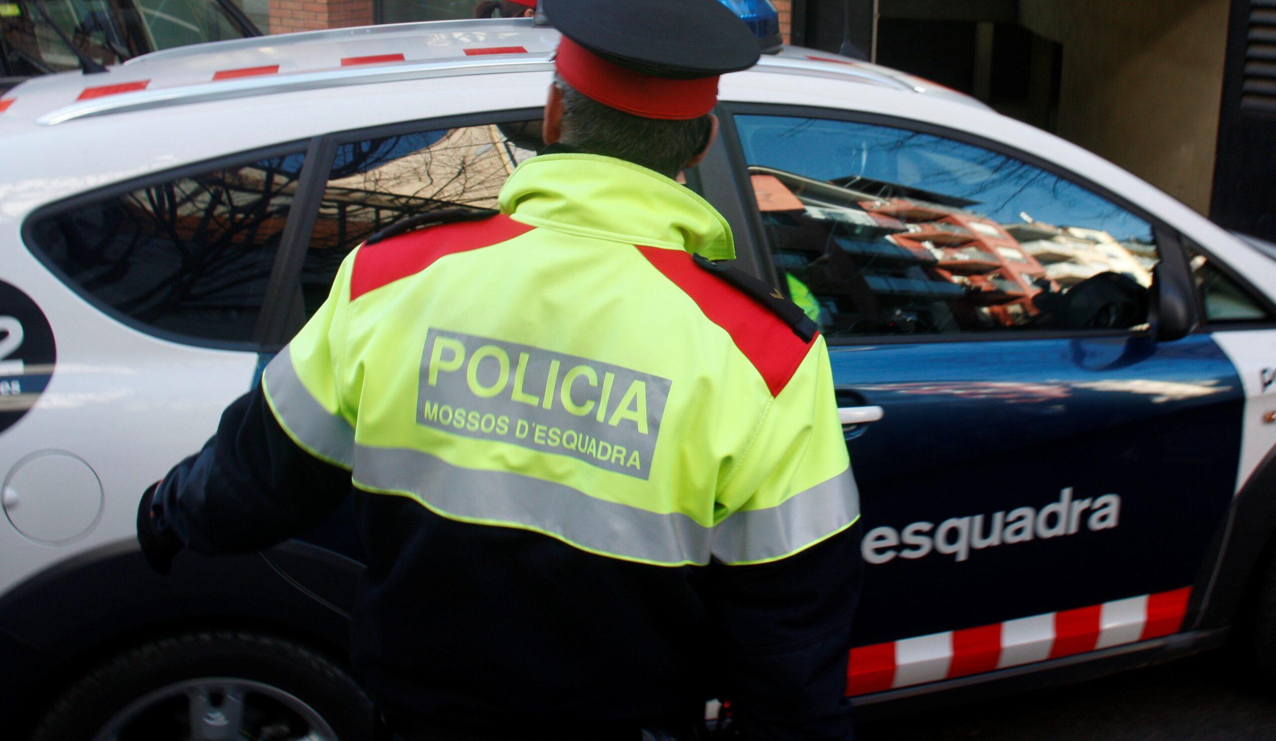 En primer pla de la imatge un agent dels Mossos d'Esquadra, i darrera el cotxe amb Fernando Blanco entrant a l'aparcament dels jutjats. Imatge del 9 de desembre de 2016. (horitzontal)